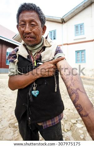 CHIN STATE, MYANMAR - JUNE 18 2015: Tattooed man with homemade pen tattoo in the Chin State Mountainous Region, Myanmar (Burma) - stock photo
