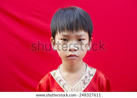 China boy in traditional Chinese red Tang suit greeting - stock photo