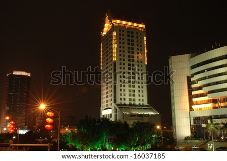 China, Guangdong province, Shenzhen city by night. Modern skyscrapers, office buildings with lights and reflections.