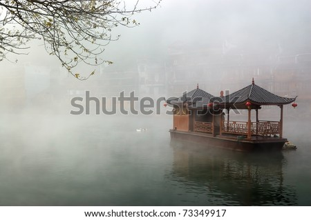 China landscape of boat on foggy river with traditional building background in Hunan province - stock photo