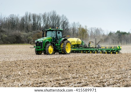 CHINA, MI, USA / APRIL 30, 2016: A tractor pulling a 16 row planter, plants corn in a China, MI field on April 30, 2016. The corn when harvested will be used for ethanol production.