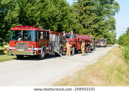 CHINA, MI, USA / JULY 24, 2014: Firefighters respond to a house fire on July 24, 2014 in China, MI. The house was not destroyed, but sustained major damage.