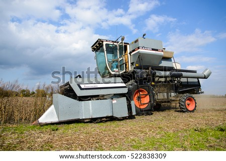 CHINA, MI, USA / OCTOBER 18, 2016: A combine is harvesting soybeans in a China, MI field on October 18, 2016. These soybeans will be transported to a grain elevator for storage.