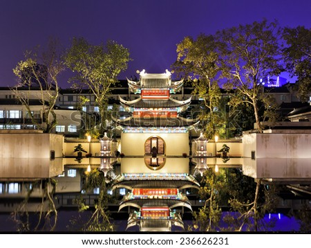 China Nanjing ancient confucius temple front view illuminated with lights at sunset with reflection in still pool with water - stock photo