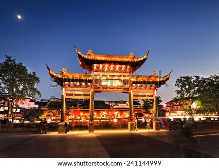 China Nanjing city area around confucius temple with wooden historic gate and background red wall with fire dragons illuminated at sunset - stock photo