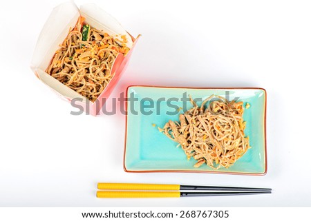 China noodles with vegetables and meat on the plate with chopsticks and take away box. Over white backfround. Top view. - stock photo