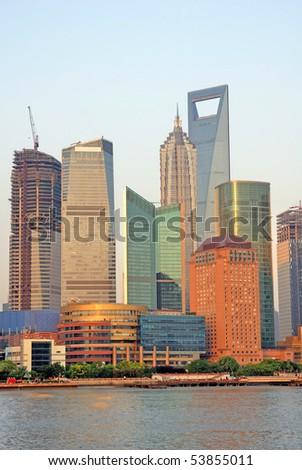 China Shanghai Pudong riverfront buildings at sunset. - stock photo