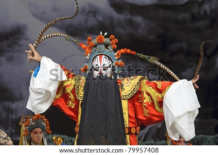 china traditional opera actor performs on stage with theatrical costume and facial painting - stock photo