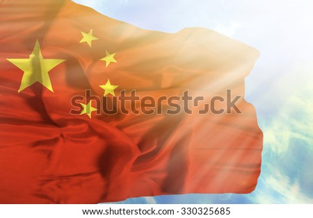 China waving flag against blue sky with sunrays - stock photo