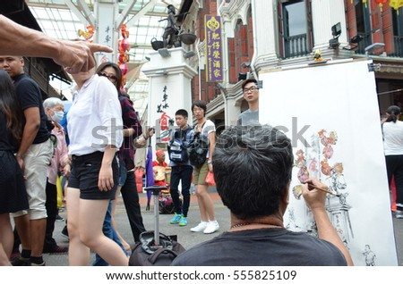 CHINATOWN, SINGAPORE - JANUARY 15, 2017: The artist sketching people, musician and chinese new year event at chinatown, Singapore