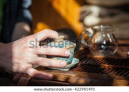 chineese teacup  in hands of teamaster on wooden room