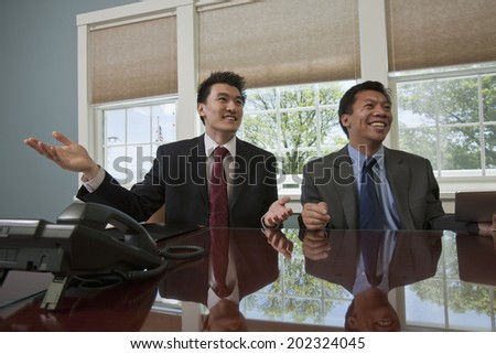 Chinese and Filipino businessmen meeting at a conference table to discuss relationships. - stock photo