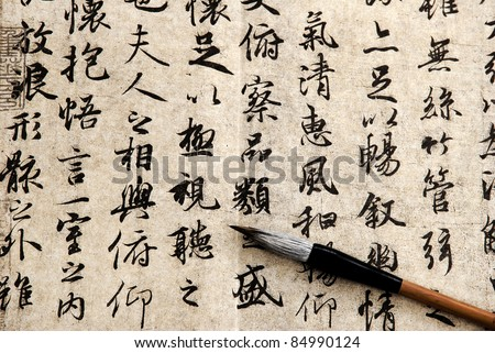 Chinese antique calligraphic text on beige paper with brush - stock photo