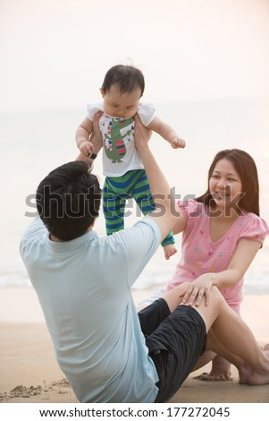 chinese asian family playing on the beach