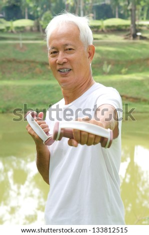 chinese Asian senior man healthy lifestyle working out on a park with a dumbbell - stock photo