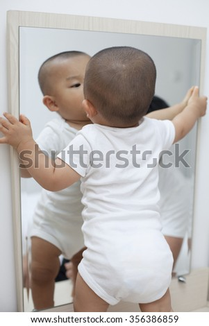 Chinese baby boy playing in front of a mirror, shot in Beijing, China - stock photo