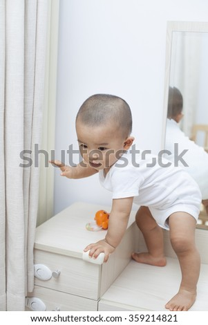 Chinese baby boy playing on a dressing table - stock photo