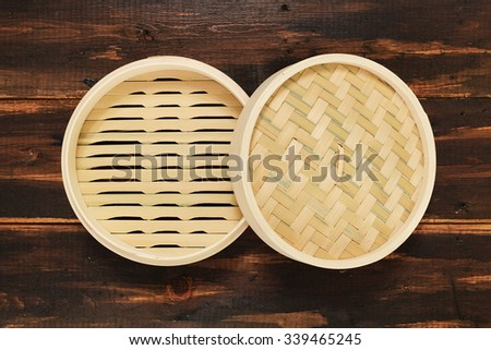 Chinese bamboo steamer top view. On brown wooden background. - stock photo