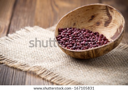 Chinese beans in wooden bowl on wooden surface. Eco product. - stock photo