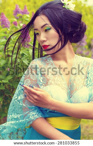 Chinese beautiful sexy girl in a kimono with a beautiful makeup with hair walking in a garden near blooming lilac bushes - stock photo