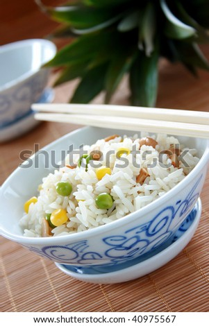Chinese bowl of egg fried rice with wooden chopsticks - stock photo