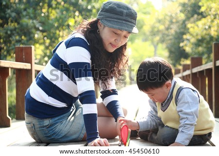 chinese boy and his mother at garden - stock photo
