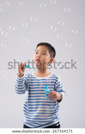 Chinese boy blowing soap bubbles