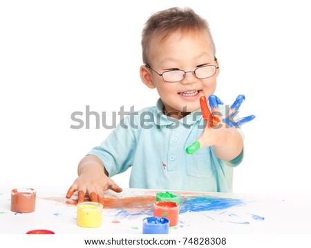 Chinese boy painting with hands with different color paint on his palms - stock photo