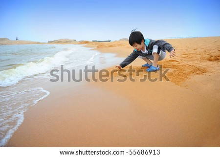 Chinese boy playing on the beach - stock photo