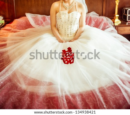 Chinese bride in the wedding dress, sitting on the bed, waiting for the groom - stock photo