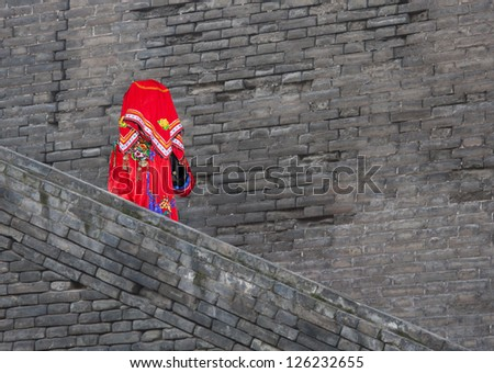 Chinese bride in traditional costumes walking down an ancient city wall - stock photo