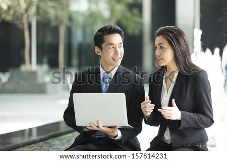 Chinese business Man and woman working together on a laptop outdoors in modern city. - stock photo