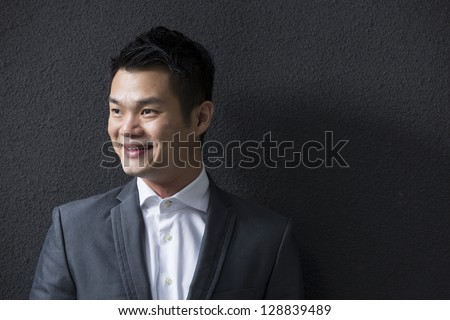 Chinese Business man leaning on a black wall. Handsome young Chinese business man leaning against a black wall and looking away. - stock photo