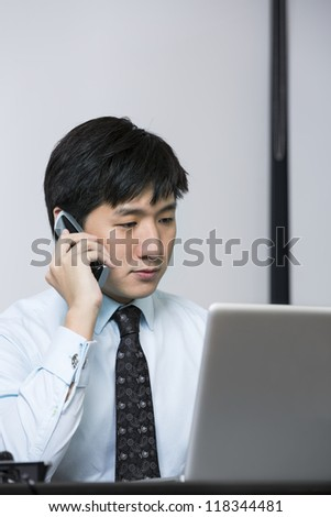 Chinese business man on phone while working on his laptop - stock photo