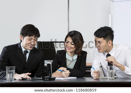 Chinese Business team having a conference phone call - stock photo