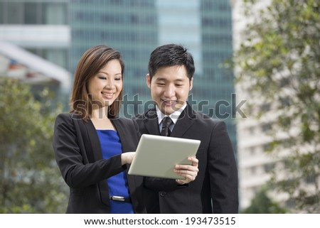 Chinese Business team meeting outside with tablet - stock photo