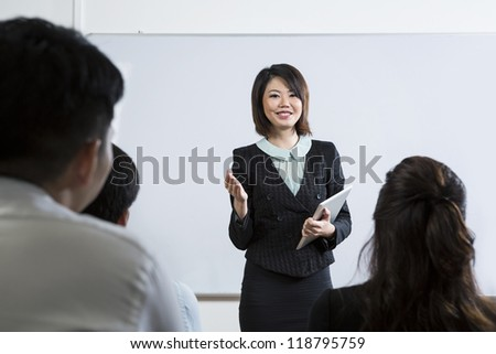 Chinese Business woman giving presentation and holding a Digital Tablet