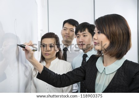 Chinese business woman writing on a whiteboard. Her team are behind her out-of-focus. - stock photo