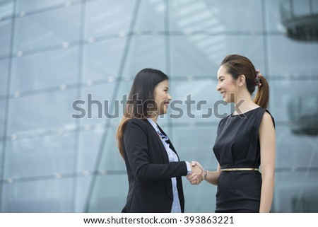 Chinese business women shaking hands outside the office. Business concept. - stock photo