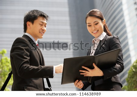 Chinese Businessman And Businesswoman Discussing Document Outside Office - stock photo