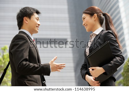 Chinese Businessman And Businesswoman Having Discussion Outside Office - stock photo