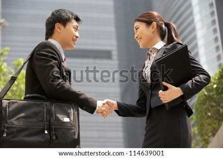 Chinese Businessman And Businesswoman Shaking Hands Outside Office - stock photo
