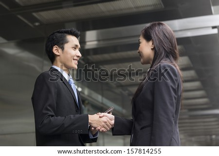 Chinese Businessman and businesswoman shaking hands outside the office - stock photo