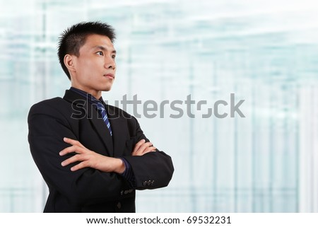 Chinese businessman in full attire looking away to empty space with blur  glass window background