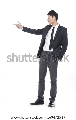 Chinese businessman in full attire pointing his hand - stock photo