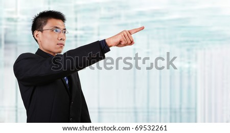 Chinese businessman in full attire pointing his hand to empty space with blur  glass window background.