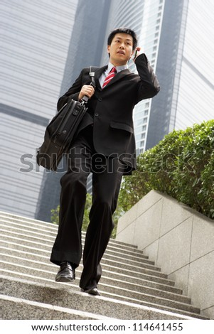 Chinese Businessman Rushing Down Steps On Mobile Phone - stock photo