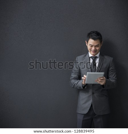 Chinese businessman using a tablet computer and leaning against a black wall. - stock photo