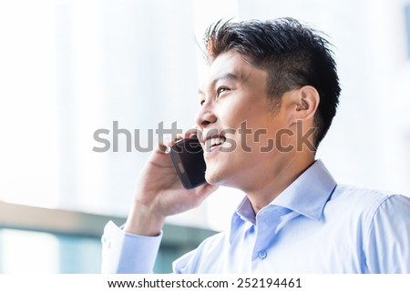 Chinese businessman using phone sitting in front of city skyline - stock photo