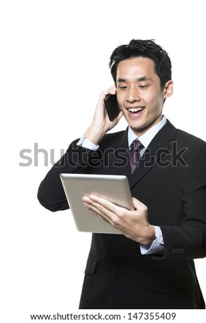 Chinese businessman with a tablet computer and talking on phone. Isolated on a white background.